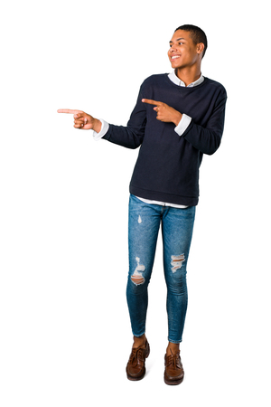 Young african american man pointing finger to the side and presenting a product while smiling on isolated white background