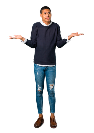 Young african american man having doubts and with confuse face expression while raising hands and shoulders on isolated white background