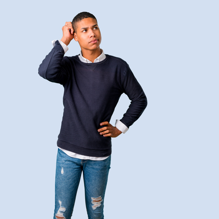 Young african american man standing and thinking an idea on isolated blue background