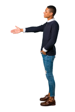 Young african american man shaking hands for closing a good deal on isolated white background