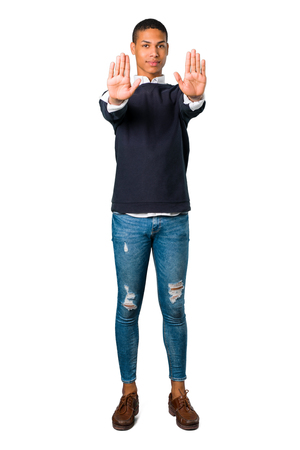 Young african american man making stop gesture with her hand denying a situation that thinks wrong on isolated white background Stock Photo