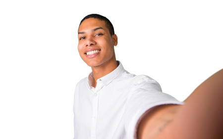 Happy young african american man  taking a selfie with the mobile on isolated white background