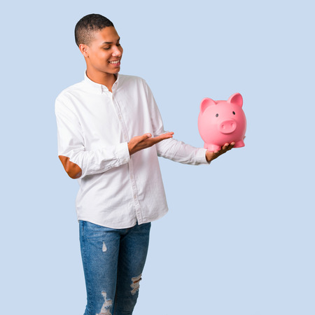 Young african american man with white shirt holding a big piggybank on isolated blue background Stock Photo