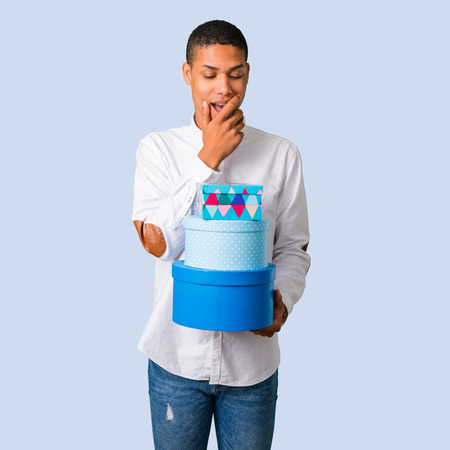 Young african american man with white shirt surprised because has been given a gift on isolated blue background Stock Photo