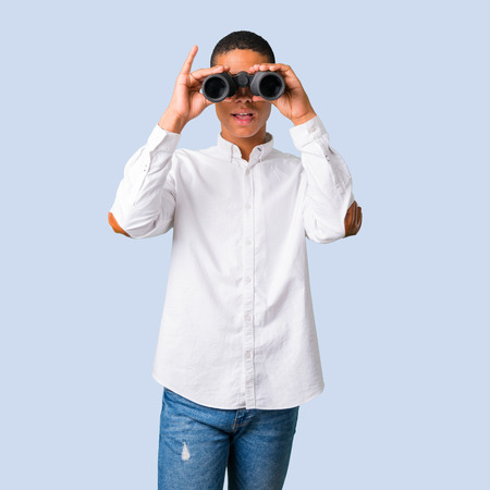 Young african american man with white shirt and looking for something in the distance with binoculars on isolated blue background