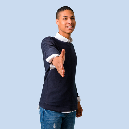 Young african american man handshaking after good deal on isolated blue background