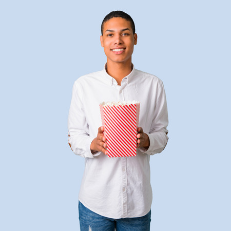 Young african american man with white shirt eating popcorns on isolated blue background Stock Photo