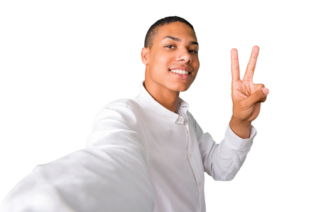 Young african american man  taking a selfie with the mobile and smiling and showing victory sign on isolated white background Stock Photo