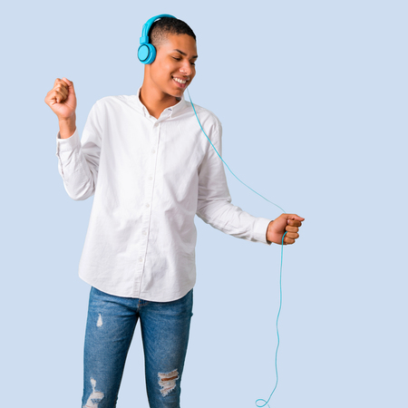 Young african american man with white shirt listening to music with headphones and dancing on isolated blue background