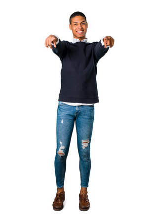 Young african american man pointing with finger at someone and laughing a lot on isolated white background