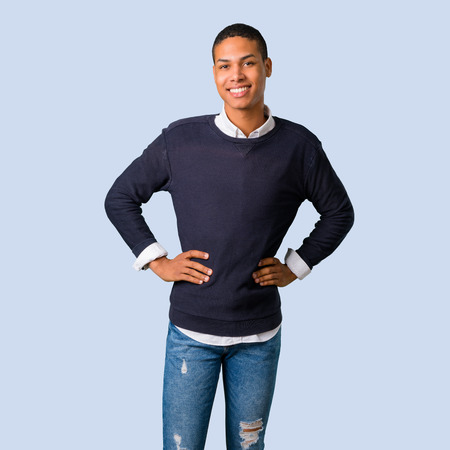 Young african american man posing with arms at hip on isolated blue background
