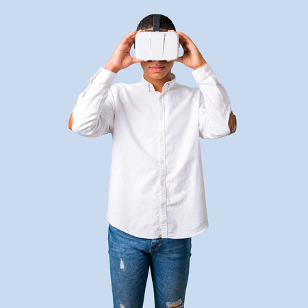 Young african american man with white shirt using VR glasses. Virtual reality experience on isolated blue background Stock Photo