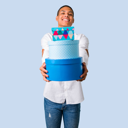 Young african american man with white shirt holding gift boxes in hands on isolated blue background