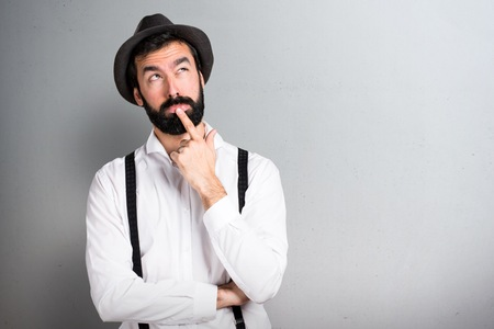 Hipster man with beard thinking on grey background Stockfoto