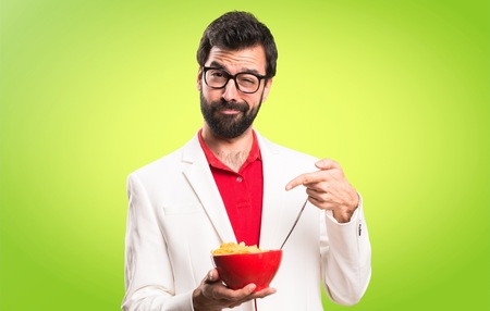 Brunette man with glasses holding a bowl of cereals on colorful background Stock Photo
