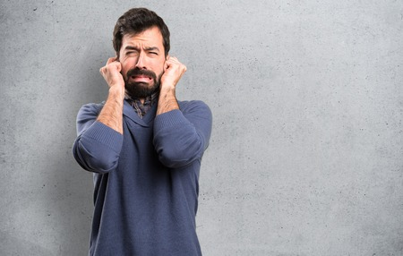 Handsome brunette man with beard covering his ears on textured background