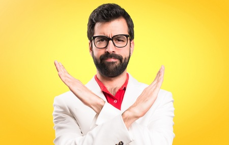 Brunette man with glasses making NO gesture on colorful background Foto de archivo