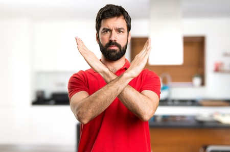 Handsome man making NO gesture inside house