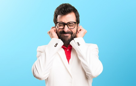 Brunette man with glasses covering his ears on colorful background Imagens
