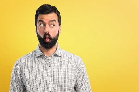 Handsome man with beard makes funny and crazy face emotion