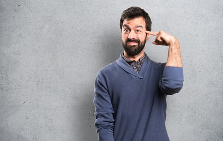 Handsome brunette man with beard making crazy gesture on textured background