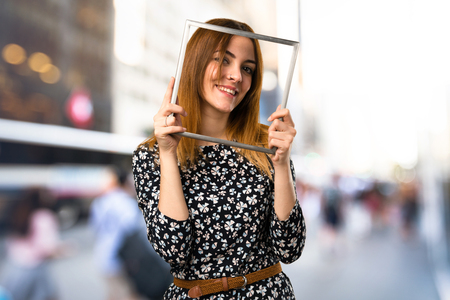 Beautiful young girl looking through an iron frame on unfocused background Imagens