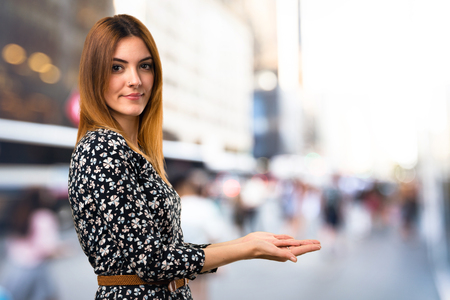 Beautiful young girl presenting something on unfocused background Imagens