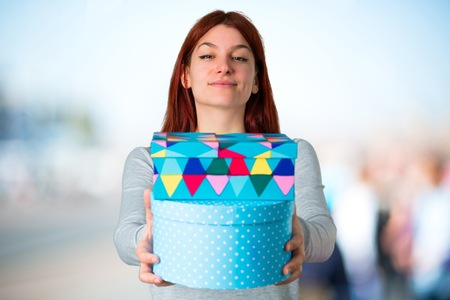Young redhead girl holding gift boxes in hands on unfocused background