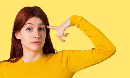 Young redhead girl with yellow sweater making the gesture of madness putting finger on the head on isolated yellow background