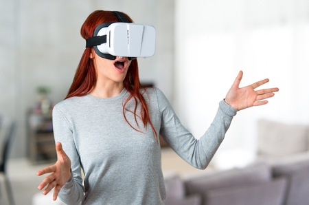 Young redhead girl using VR glasses. Virtual reality experience on unfocused background