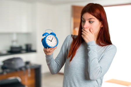 Young redhead girl holding vintage alarm clock on unfocused background Imagens
