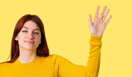 Young redhead girl with yellow sweater saluting with hand with happy expression on isolated yellow background Stock Photo
