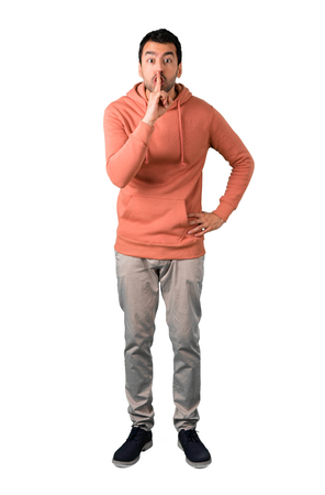 Full body of Man in a pink sweatshirt showing a sign of closing mouth and silence gesture putting finger in mouth on isolated white background