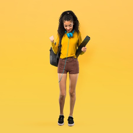 Full body of Teenager student girl with curly hair celebrating a victory and happy for having won a prize on yellow background Archivio Fotografico