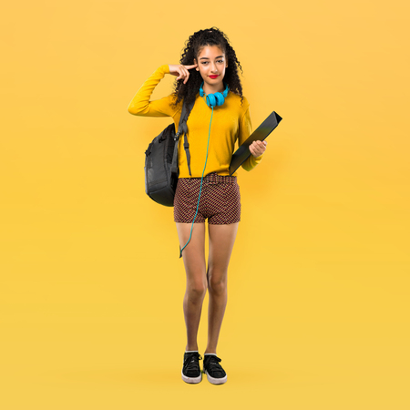 Full body of Teenager student girl with curly hair covering both ears with hands. Frustrated expression on yellow background