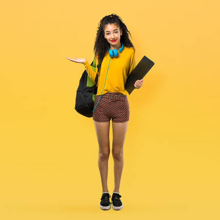 Full body of Teenager student girl with curly hair having doubts and with confuse face expression while raising hands and shoulders on yellow background