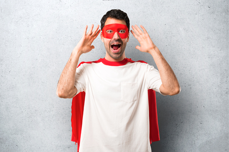 Superhero man with mask and red cape with surprise and shocked facial expression. Gaping because can not believe what is happening on textured grey background Stok Fotoğraf