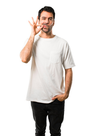 Young man with white shirt showing a sign of closing mouth and silence gesture doing like closing his mouth with a zipper on isolated white background