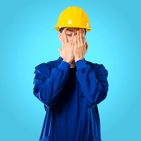 Young workman with helmet covering eyes by hands and looking through the fingers on blue background