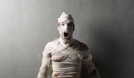 Terrorific mummy screaming on textured wall background.  Halloween holidays Stock fotó