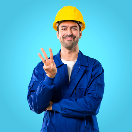 Young workman with helmet happy and counting three with fingers on blue background Archivio Fotografico