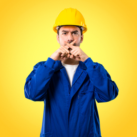 Young workman with helmet showing a sign of closing mouth and silence gesture on yellow background Stock Photo