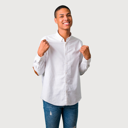 Young african american man proud and self-satisfied in love yourself concept on grey background