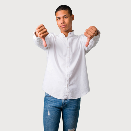 Young african american man showing thumb down with both hands. Negative expression on grey background