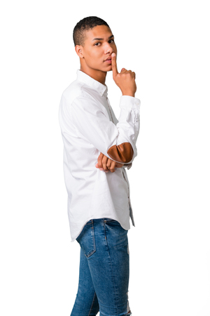Young african american man with white shirt showing a sign of closing mouth and silence gesture putting finger in mouth on isolated white background Stock Photo