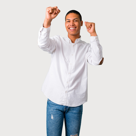 Young african american man celebrating a victory and surprised to be successful on grey background Archivio Fotografico