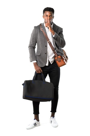 Full body of African american business man traveling with suitcases showing a sign of closing mouth and silence gesture putting finger in mouth on white background