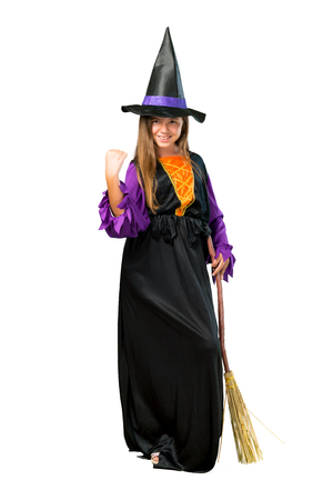 A full-length shot of a Little girl dressed as a witch for halloween holidays celebrating a victory isolated on white