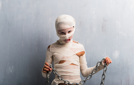 Boy in mummy costume with chains for halloween holidays