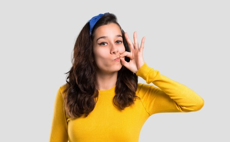 Young girl with yellow sweater and blue bandana on her head showing a sign of closing mouth and silence gesture doing like closing his mouth with a zipper on isolated grey background